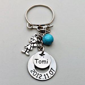 Babafiú, baba kulcstartó. A gravírozott kulcstartón a gyermek neve és születési dátuma szerepelhet. Az egyedi kulcstartóra választhatsz díszítő fityegőket is.