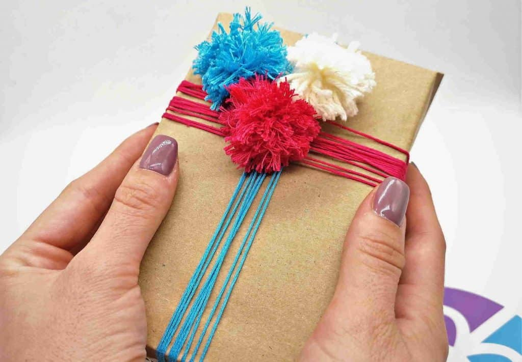 Ajándék csomagolás kék piros pompom dísszel